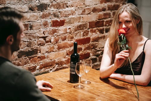 Young couple in elegant clothes sitting at wooden table near brick wall in light restaurant while enjoying date with red rose and wine near glasses and looking at each other