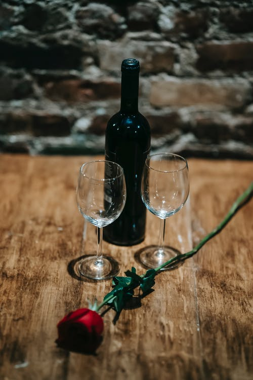 茶色の木製テーブルのワイングラスの横にある黒いガラス瓶