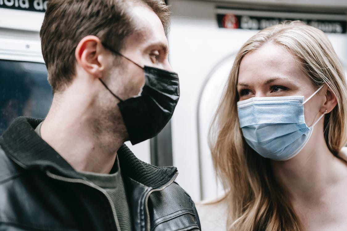 Anonymous couple in masks in subway train