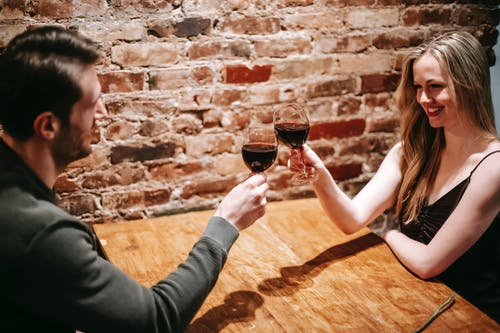 Couple having romantic dinner in cafeteria cheering with wineglasses