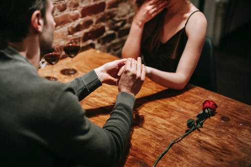 Crop unrecognizable couple in elegant clothes sitting in cafeteria at table with wine in glasses and rose near brick wall while having romantic dinner and holding hand while making proposal