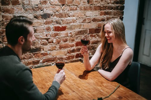 Side view of young smiling couple in elegant clothes sitting in cafeteria at table near brick wall while having romantic dinner with wine in glasses and looking at each other