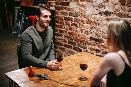 坐在棕色的木桌旁边的灰色毛衣的男人