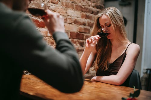 Young mand and woman drinking red wine having rest in restaurant