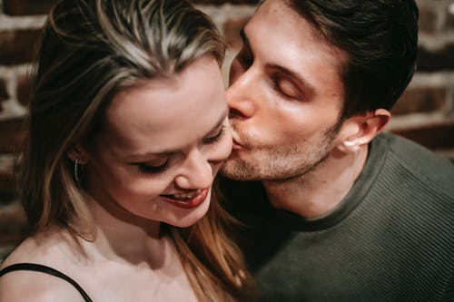 Happy young man kissing girlfriend in room