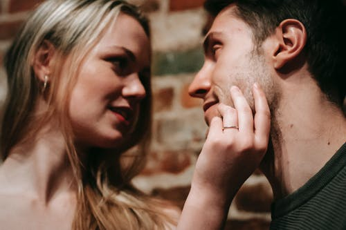 Young smiling blond woman touching face of boyfriend while spending together romantic weekend