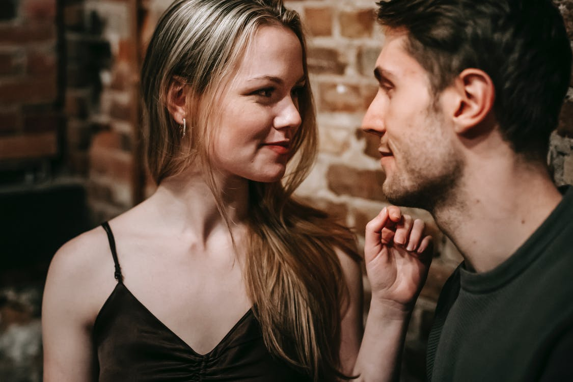 Young man and woman looking at each other enjoying romantic date together in cafe