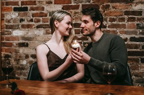 Happy young couple in elegant clothes sitting at table and celebrating birthday with small cupcake and candle near glasses with red wine and brick wall while looking at each other