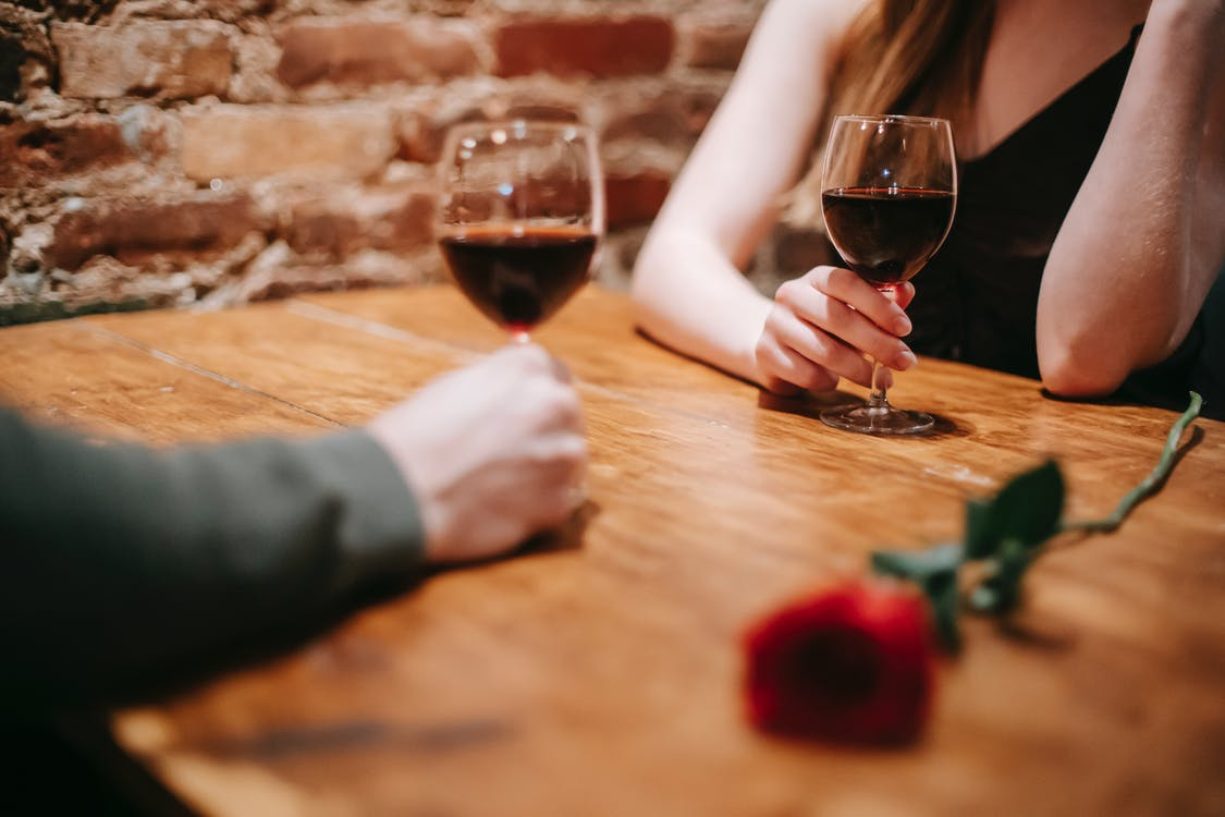 Crop anonymous couple in elegant outfits enjoying romantic date in bar at table with red rose and glasses with wine near brick wall