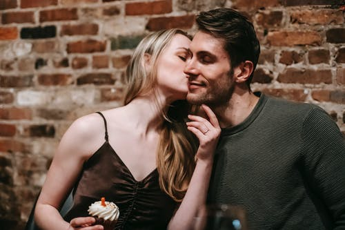 Couple kissing while celebrating birthday with cupcake in restaurant