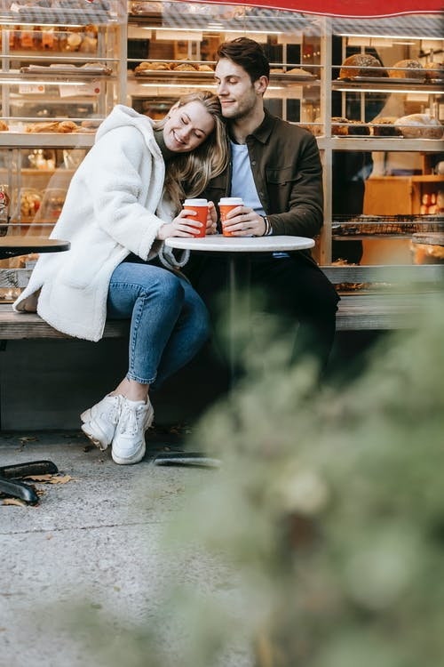 Happy young couple in warm clothes sitting in city near building at round table in street cafe with coffee cups in hands while leaning on shoulder in daylight