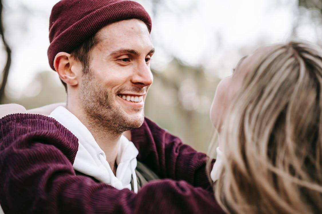 мужчина в темно бордовой вязаной шапке улыбается