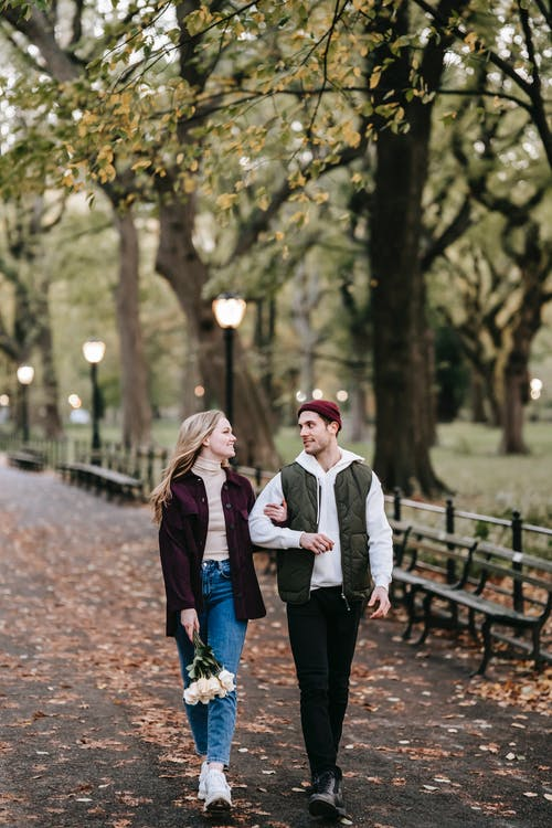 Couple strolling with flowers in autumn in park