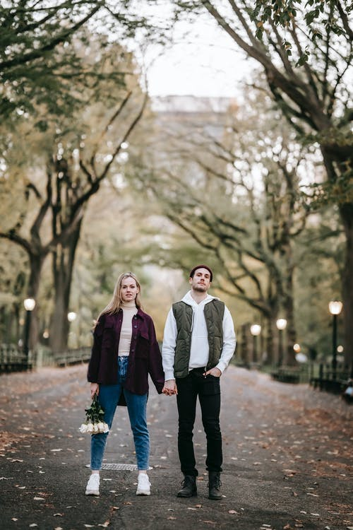 Full body of confident young couple in outerwear standing in park together with bouquet of flowers while holding hands in autumn in daytime near trees and looking at camera