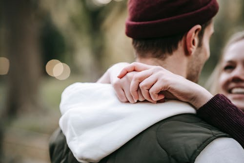 Unrecognizable happy couple hugging in park