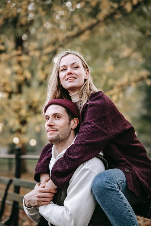 Young couple in warm clothes spending time in street while sitting on bench and embracing in daylight while looking away