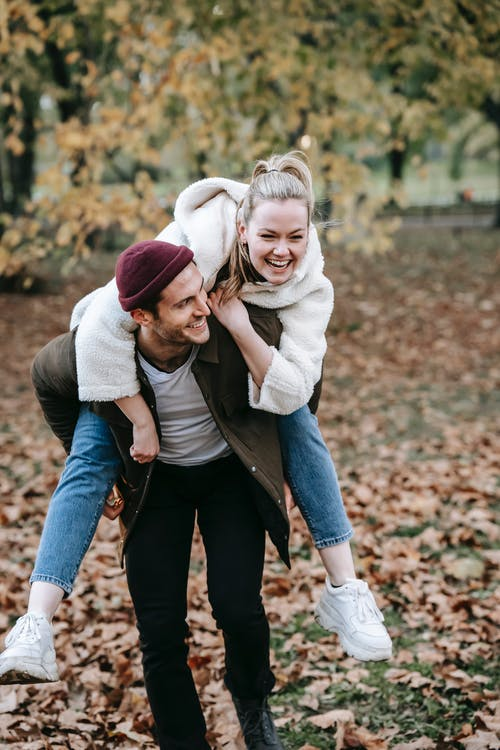 Smiling young couple in warm clothes spending time in street while man giving piggyback ride to woman in daylight near trees in autumn and grass with foliage