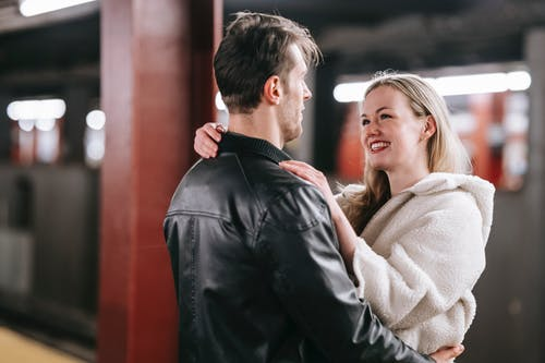 Smiling couple looking at each other and embracing while standing on platform of metro with train on blurred background during date