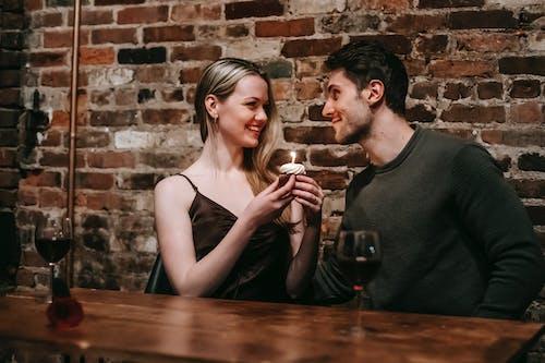 從黑色水箱旁的女人旁邊的透明水杯喝水的黑色圓領襯衫的男人