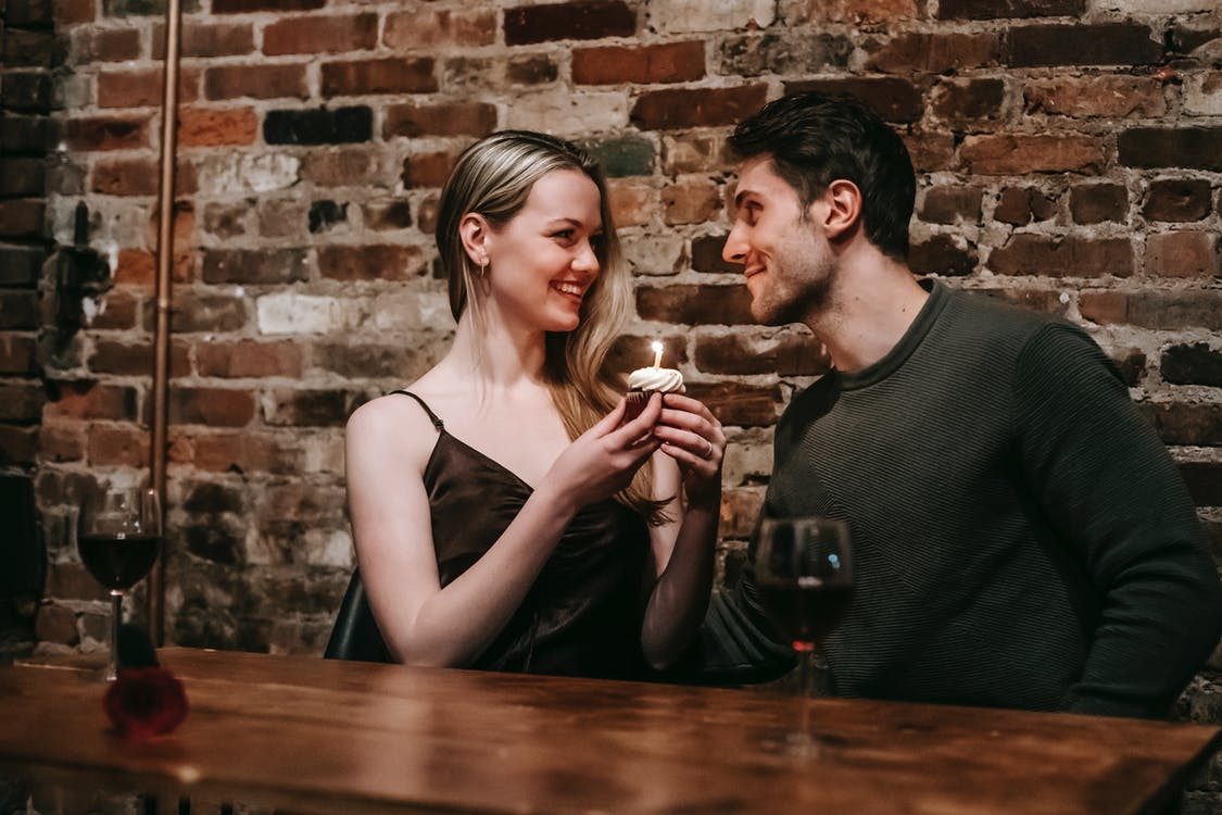 Side view of loving couple sitting near brick wall at wooden table with cupcake with burning candle looking at each other while celebrating anniversary in cafe
