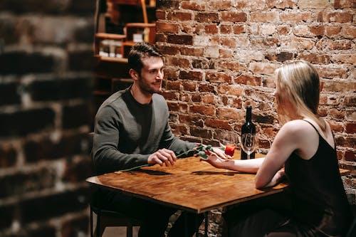 坐在灰色長袖襯衫的女人旁邊的灰色毛衣的男人