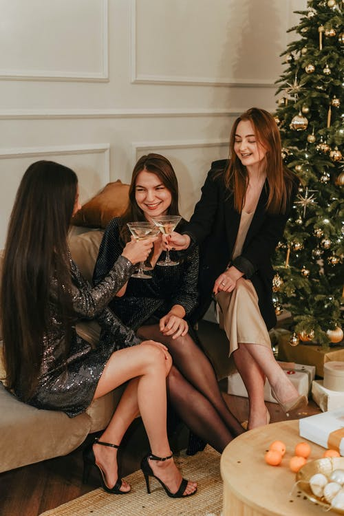 Three Women Sitting on Couch With Drinks