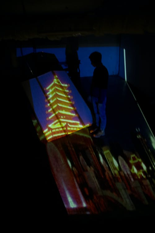 Man near picture of Chinese pagoda