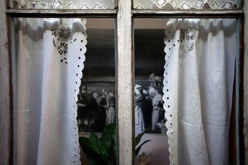 Window with vintage curtains of room with old photo