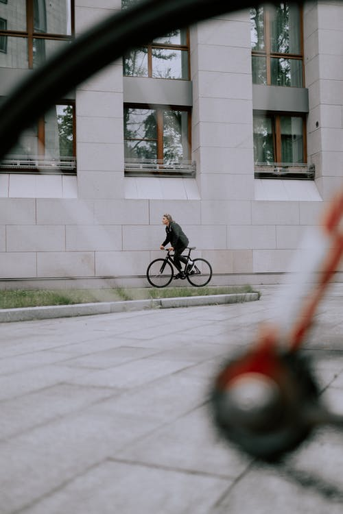 Man in Black Jacket Riding Bicycle on the Street