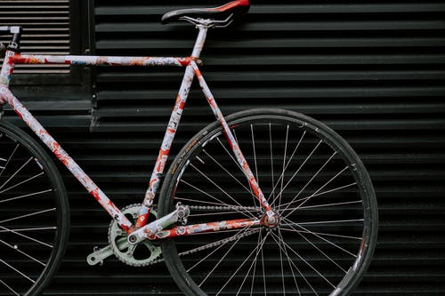 Red and Black Bicycle Leaning on Black Metal Wall