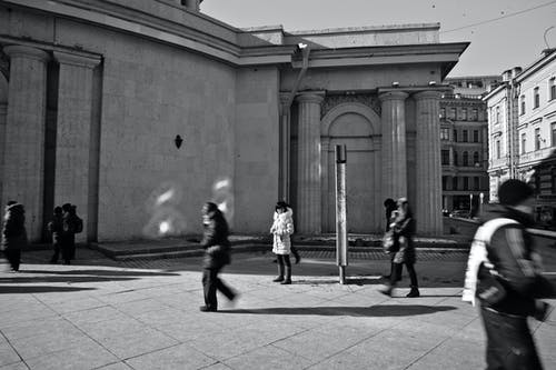 Black and white of crowd of people walking on city street in downtown against historical buildings in sunny day