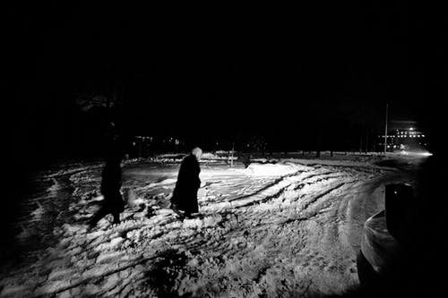 People walking on snowy road in evening time