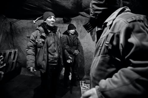 Black and white of men in outerwear in shelter for homeless people in poverty