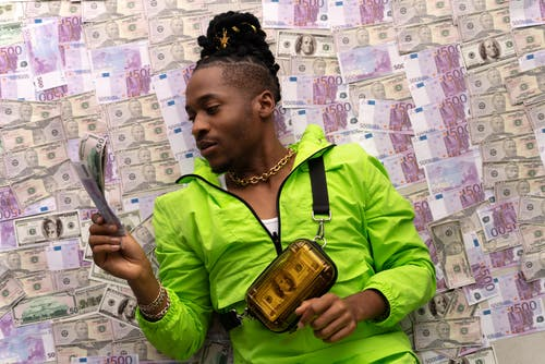 Man in Green Jacket Lying Down on Money