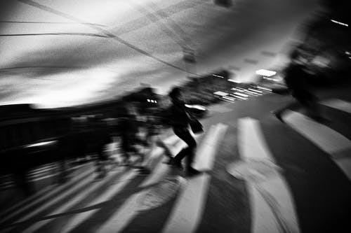 Black and white of anonymous pedestrians crossing asphalt road on zebra in city
