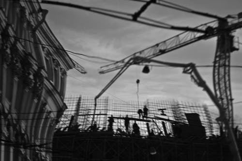 Silhouettes of builders on construction site