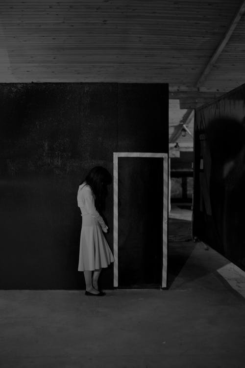 Black and white of full body side view anonymous spooky female with long dark hair in white dress standing near wall