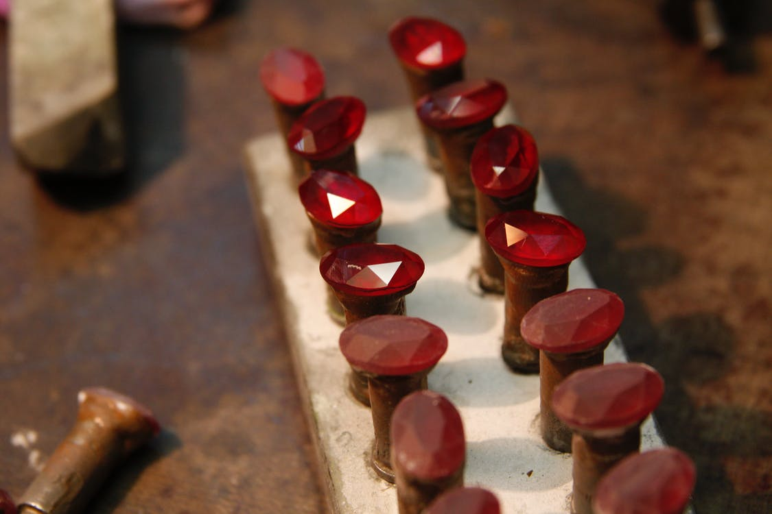 From above of red ruby stones collection on wooden board in jewelers workshop