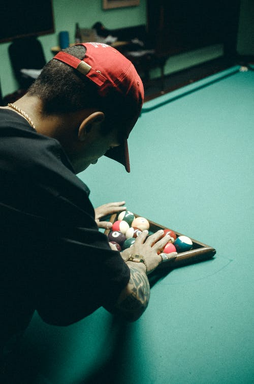 Man in Black T-shirt and Red Baseball Cap Arranging Billiard Balls on Table
