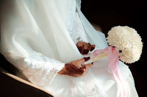 Woman in White Wedding Dress Holding White Bouquet