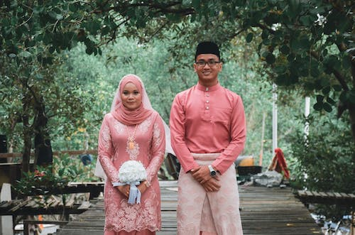 Man in Pink Thobe Standing Beside Woman in Pink Hijab