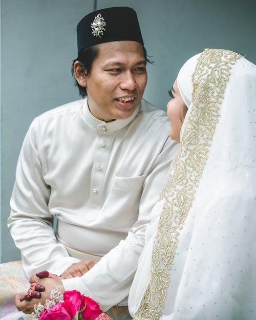 Man in White Thobe Sitting Beside Woman in White Dress