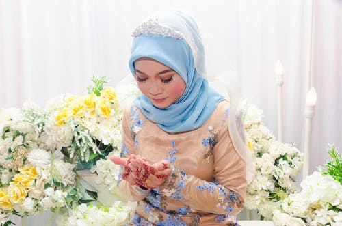 Woman in Brown Hijab Holding Bouquet of Flowers
