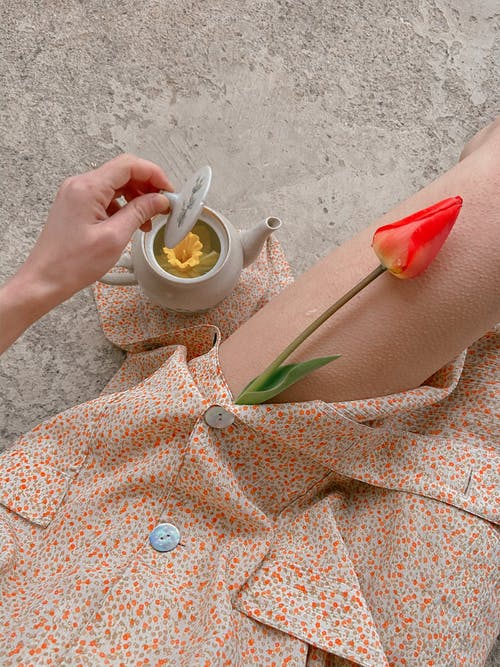 Woman with teapot with flower tea and tulip