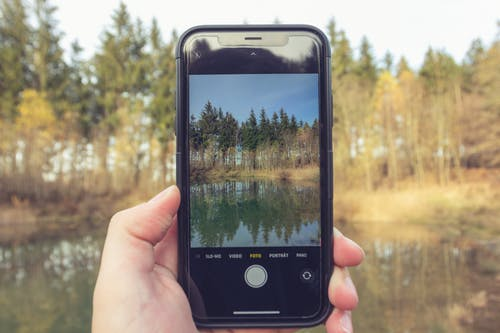 Crop anonymous person taking photo of forest and calm water of river with mobile phone on blurred background of nature