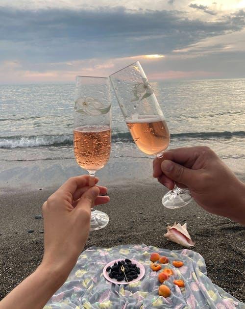 Пара звенящих бокалов шампанского на берегу моря