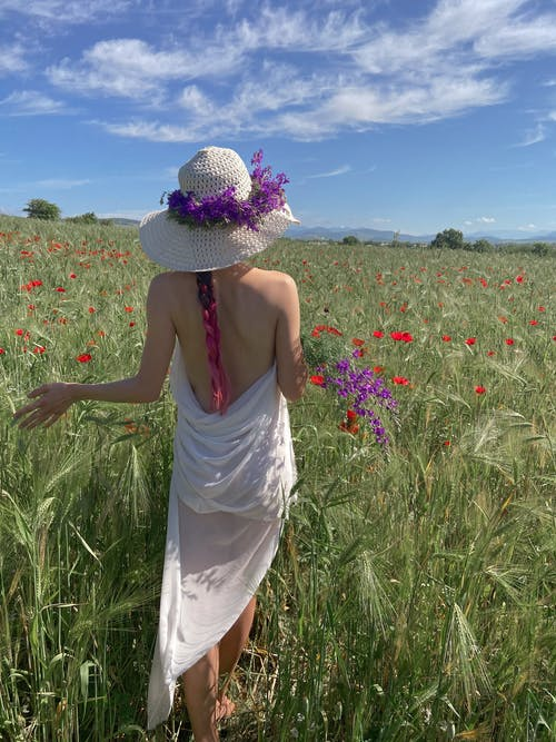 Back view of anonymous female wearing straw hat carrying blooming bouquet of flowers in meadow in summer day