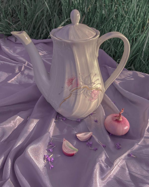 Ceramic teapot and onion on silk cloth