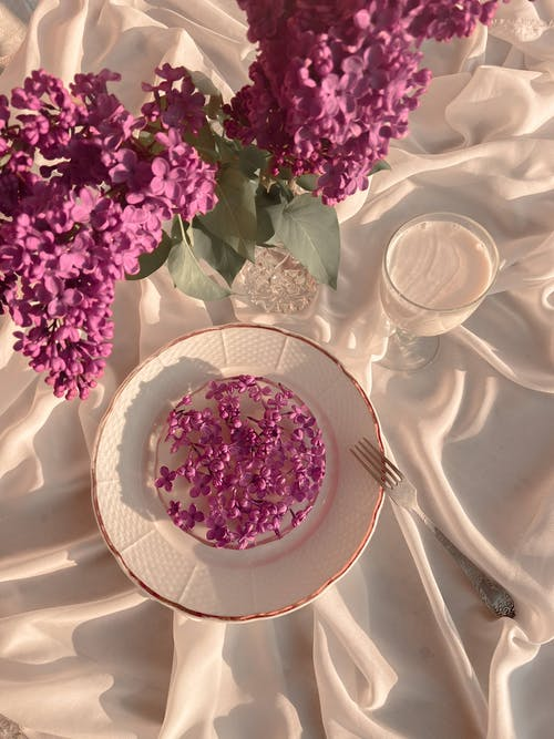 Top view of arranged bouquet of fresh flowers of lilac with plate of frozen flowers and fork near goblet of milk