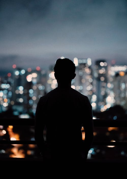 Silhouette of man standing on balcony at night